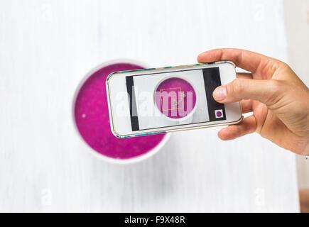 Donna di scattare una foto di drago frullato di frutta con il suo smartphone, close-up Foto Stock
