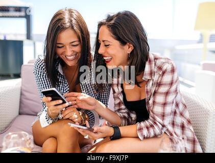 Due happy amici di sesso femminile sulla terrazza che guarda al telefono cellulare Foto Stock