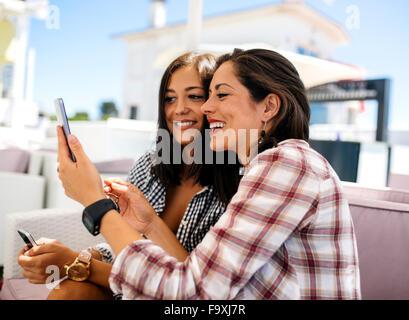 Due happy amici di sesso femminile sulla terrazza prendendo un selfie Foto Stock