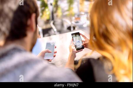 Vista posteriore della coppia giovane seduto a fianco a fianco con il suo smartphone Foto Stock