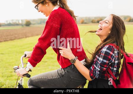 Felice di due giovani donne che condividono una bicicletta nel paesaggio rurale Foto Stock
