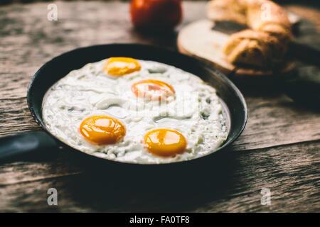 Uovo fritto in padella su di un tavolo di legno Foto Stock