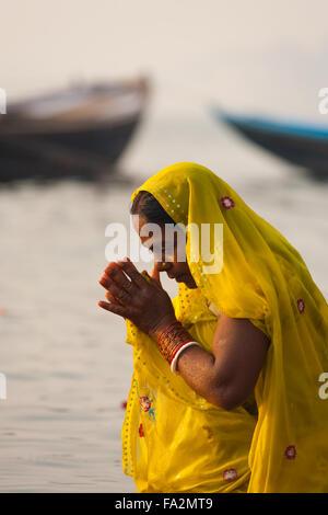 Una pia donna indù in giallo sari inarcamento, pregando e balneazione con le mani incrociate insieme nel sacro Gange Foto Stock