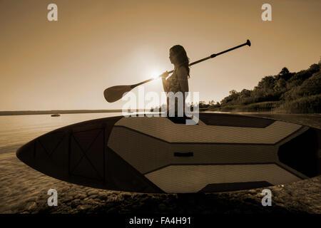 Donna matura portante stand up paddle board sul lungolago, Baviera, Germania Foto Stock
