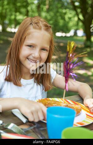 Ritratto di una ragazza a mangiare cibo a picnic, Monaco di Baviera, Germania Foto Stock