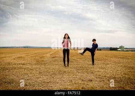 Traino di adolescente giocando su un campo di raccolto Foto Stock