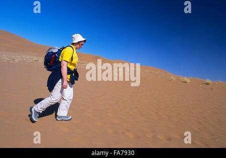 La Namibia, Namib-Naukluft National Park, Sossusvlei, Donna che cammina nel deserto // Namibie, Namib-Naukluft National Foto Stock