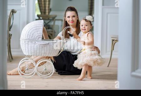 Madre osservando il suo grazioso baby giocando carrello Foto Stock
