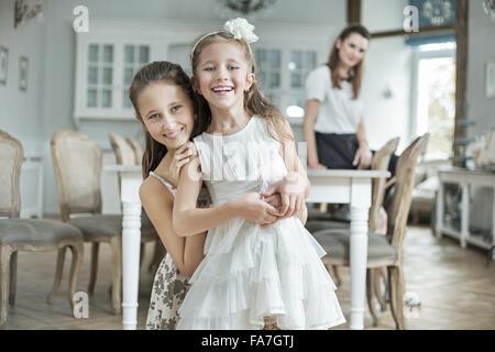 Due figlie allegra posa con bella madre Foto Stock
