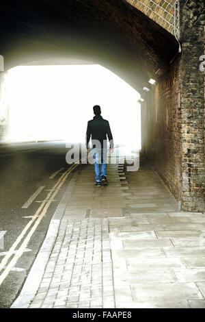 Uomo che cammina attraverso il Tunnel urbano Foto Stock