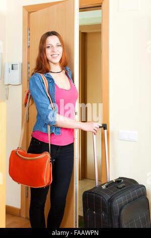 Positivo giovane donna con la valigia porta vicino a casa Foto Stock