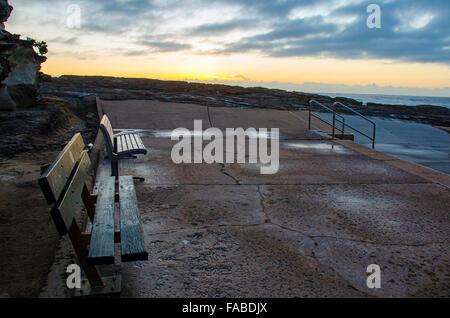 Posti vuoti per guardare verso il sole che sorge in un oceano piscina accanto alla spiaggia di acqua dolce a Sydney Foto Stock