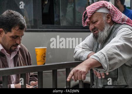 Due uomini arabi in abito moderno e gli altri in abito tradizionale, Amman, Giordania Foto Stock
