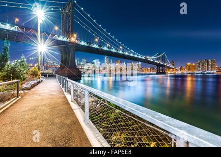 Manhattan Bridge di notte, visto da John Street Park con il ponte di Brooklyn e la parte inferiore dello skyline di Manhattan in background. Foto Stock