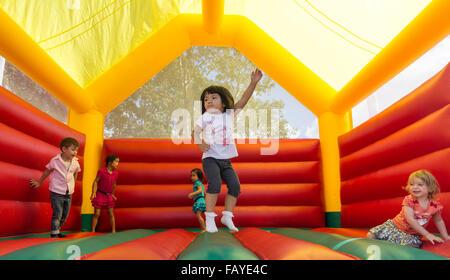 Carino divertente asilo bambina giocando, saltando sul castello di salto Foto Stock