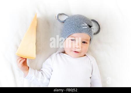 Baby boy in mouse hat giacente su una coperta con formaggio Foto Stock