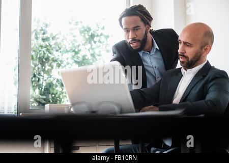 Due imprenditori lavora con il computer portatile da scrivania in ufficio Foto Stock