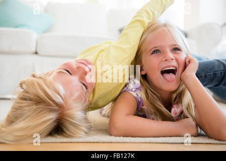 Ragazzo (4-5) e la ragazza (6-7) giocando sul pavimento Foto Stock