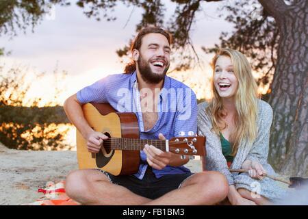 Coppia giovane a suonare la chitarra dal lago Foto Stock