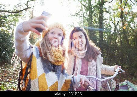 Le ragazze adolescenti nella foresta utilizzando smartphone per prendere selfie sorridente Foto Stock