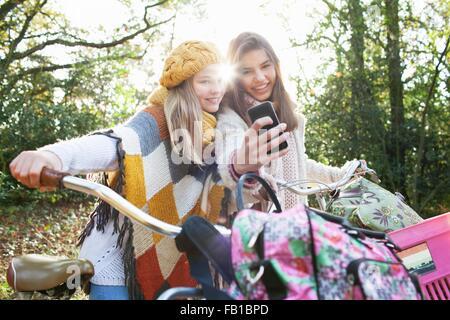 Le ragazze adolescenti nella foresta azienda biciclette utilizza lo smartphone per prendere selfie sorridente Foto Stock