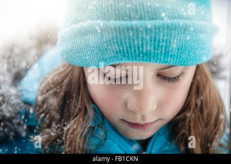 Close up ritratto della ragazza che indossa knit hat guardando giù, nevicava Foto Stock