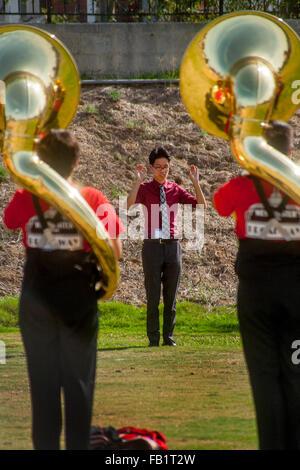 Un Vietnamese-American high school marching band direttore conduce la sua multirazziale tuba i giocatori in pratica Foto Stock