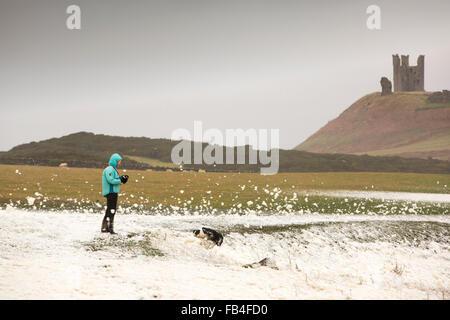 Una donna di supporti antisismici la tempesta circondato dalla schiuma wipped fino dalla tempesta di soffiatura onde a riva di Craster sulla costa di Northumberland con Dunstanburgh Castle in background. Adottata lunedì 4 gennaio 2016