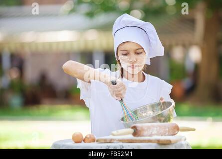 Little Chef monta le uova in una terrina all'aperto Foto Stock