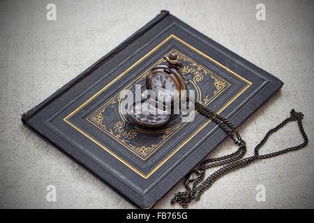 Vintage vita ancora con orologio da tasca e vecchio libro Foto Stock