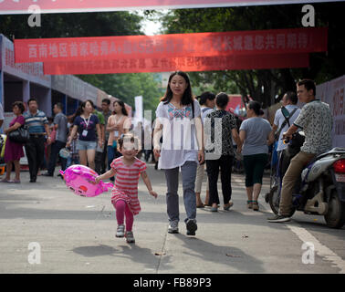 Un misto di gara toddler corre davanti a sua madre cinese a una fiera commerciale in una città in Cina. Foto Stock