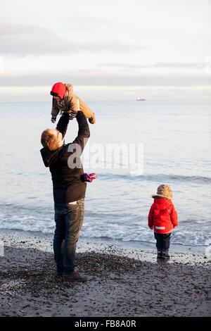 Danimarca, Grenen, Padre con figlie (6-11 mesi) ( 2-3) giocando sulla spiaggia Foto Stock