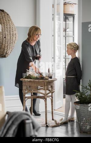 La Svezia, nonna con nipote (6-7) in piedi nel soggiorno durante il periodo di Natale Foto Stock