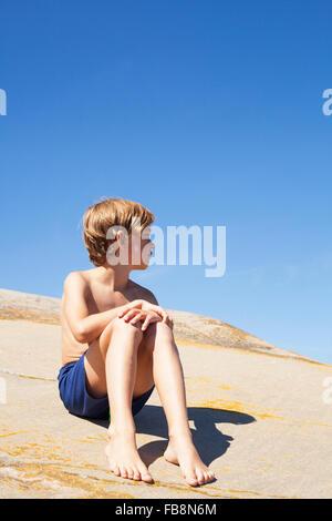 La Svezia, Uppland, Runmaro, Barrskar, ragazzo (6-7) seduto sul rock in estate Foto Stock