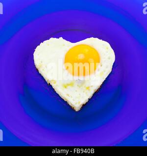 A forma di cuore ad uovo sul piatto blu