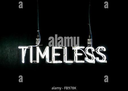 Illuminato bianco neon Timeless firmare al buio su un fondo nero con copia spazio sopra Foto Stock