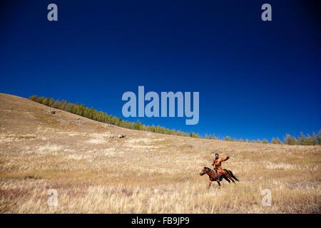 Un herder cavallo al galoppo attraverso Gorkhi Terelj National Park, Mongolia. Foto Stock
