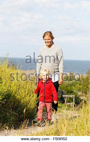 La Svezia, arcipelago di Stoccolma, Sodermanland, Oja, Donna camminare con il figlio (2-3) lungo il percorso attraverso Foto Stock