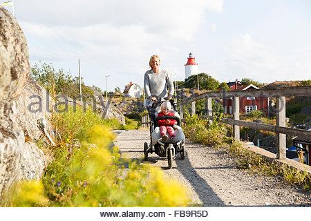 La Svezia, arcipelago di Stoccolma, Sodermanland, Oja, Donna a piedi lungo la strada sterrata con figlio (2-3) in Foto Stock