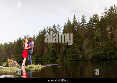La Svezia, Vastmanland, Bergslagen, Svartalven, metà adulto giovane abbracciando in fiume Foto Stock