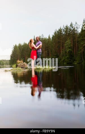 La Svezia, Vastmanland, Bergslagen, Svartalven, metà adulto giovane abbracciando Foto Stock