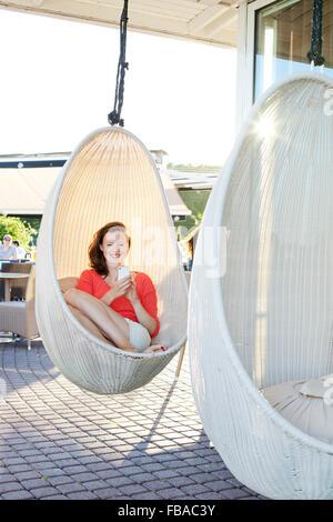 Finlandia, Uusimaa, Helsinki, Kaivopuisto, sorridente giovane donna utilizzando smart phone nella sedia di oscillazione