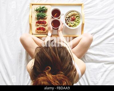 Direttamente sopra il colpo di donna con colazione a letto Foto Stock