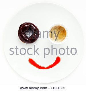 La faccina sorridente fatta di ciambella e la tazza di caffè sulla piastra Foto Stock