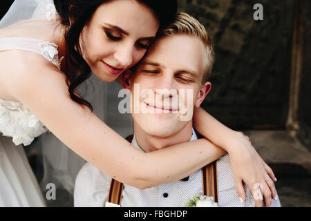 Sposa poggiando su lo sposo Foto Stock