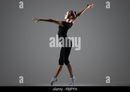 Bella giovane montare ginnasta atleta donna in abbigliamento sportivo che lavora fuori, ballare sulla tiptoes, fare Foto Stock