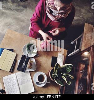 Angolo di Alta Vista di metà donna adulta seduti a casa Foto Stock