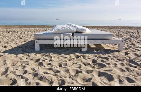 White lettino sulla spiaggia sabbiosa con vista oceano su una mattina di sole in Ibiza, Spagna. Foto Stock