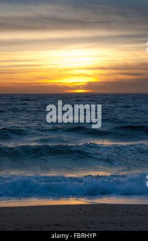 Colorato tramonto sull'oceano con onde che si infrangono sulla riva aringhe Cove Beach, Cape Cod, Massachusetts. Foto Stock