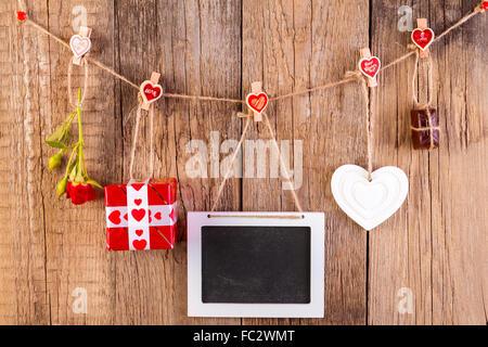 Red Rose con confezione regalo e una cornice bianca e cioccolato su sfondo di legno. Il concetto di amore.
